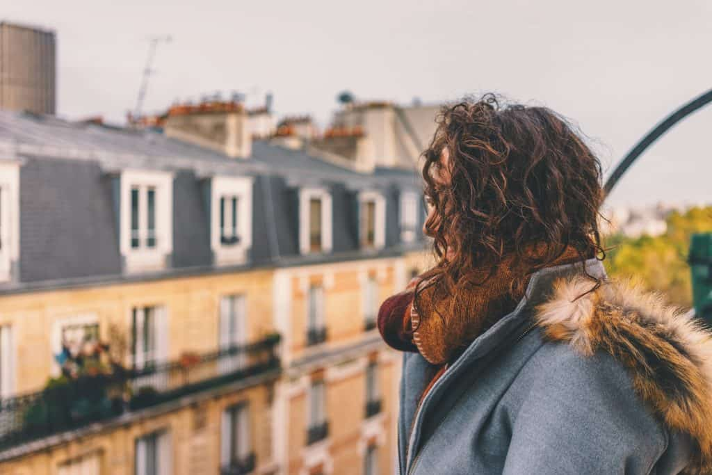 Woman on rooftop looking at flats - UK Property Cash buyers