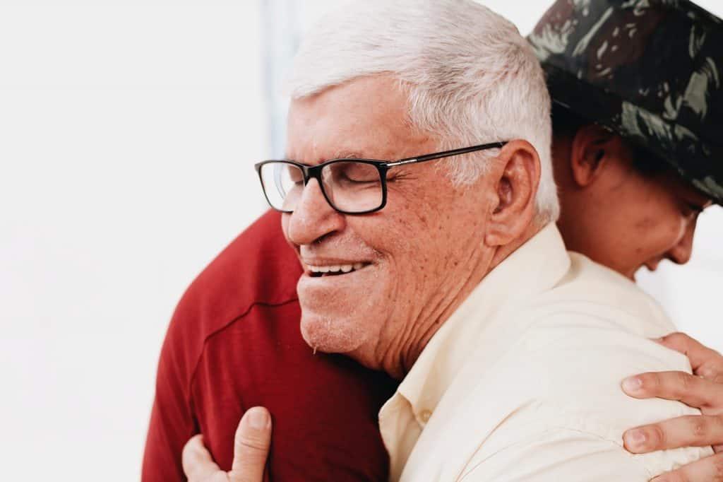 Happy elderly man hugging family - UK Property Cash Buyers